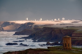 The octagonal 'Temple of the Winds' at Bude, North Cornwall, modelled on the 'Tower of the Winds' in Athens, was built by Bude's famous Acland Family in 1840 and moved to the present location in 1880. The headland is now known as 'Compass Point' after the markings of the cardinal and ordinal directions on its exterior walls. It provides a good source of foreground interest in any shot up the coast from here, though the light and drama is rarely as good as in this shot. At low tide an unbroken beach leads all the way up to the sunlit headland; behind it, and greatly foreshortened in this scene, the radar dishes of GCHQ Bude, built on the former WWII airfield of RAF Cleave, lie nearly 8km up the coast. A big Atlantic winter storm was hitting the coast, and it was this that I had gone out to photograph at dawn; I was not aware until I got there that snow had fallen in the night, and was fortunate to get the sun coming through to light it, and the radar dishes, during an all too brief break in the clouds.